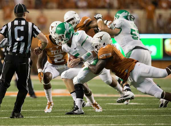 SACKED. Texas defenders DeMarco Cobbs and Mykkele Thompson sack North Texas quarterback Andrew McNulty (Photo: Don Bender).