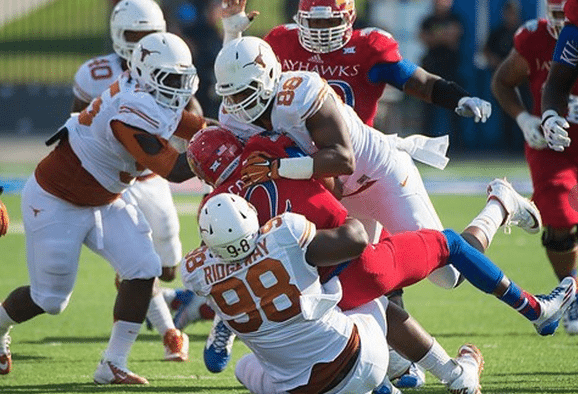 Hassan Ridgeway and Cedric Reed swarm a Kansas player (Photo: courtesy Texasports.com).