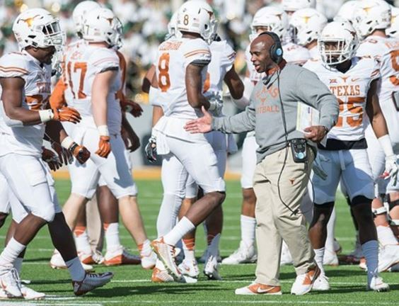 Charlie Strong high fives a player.