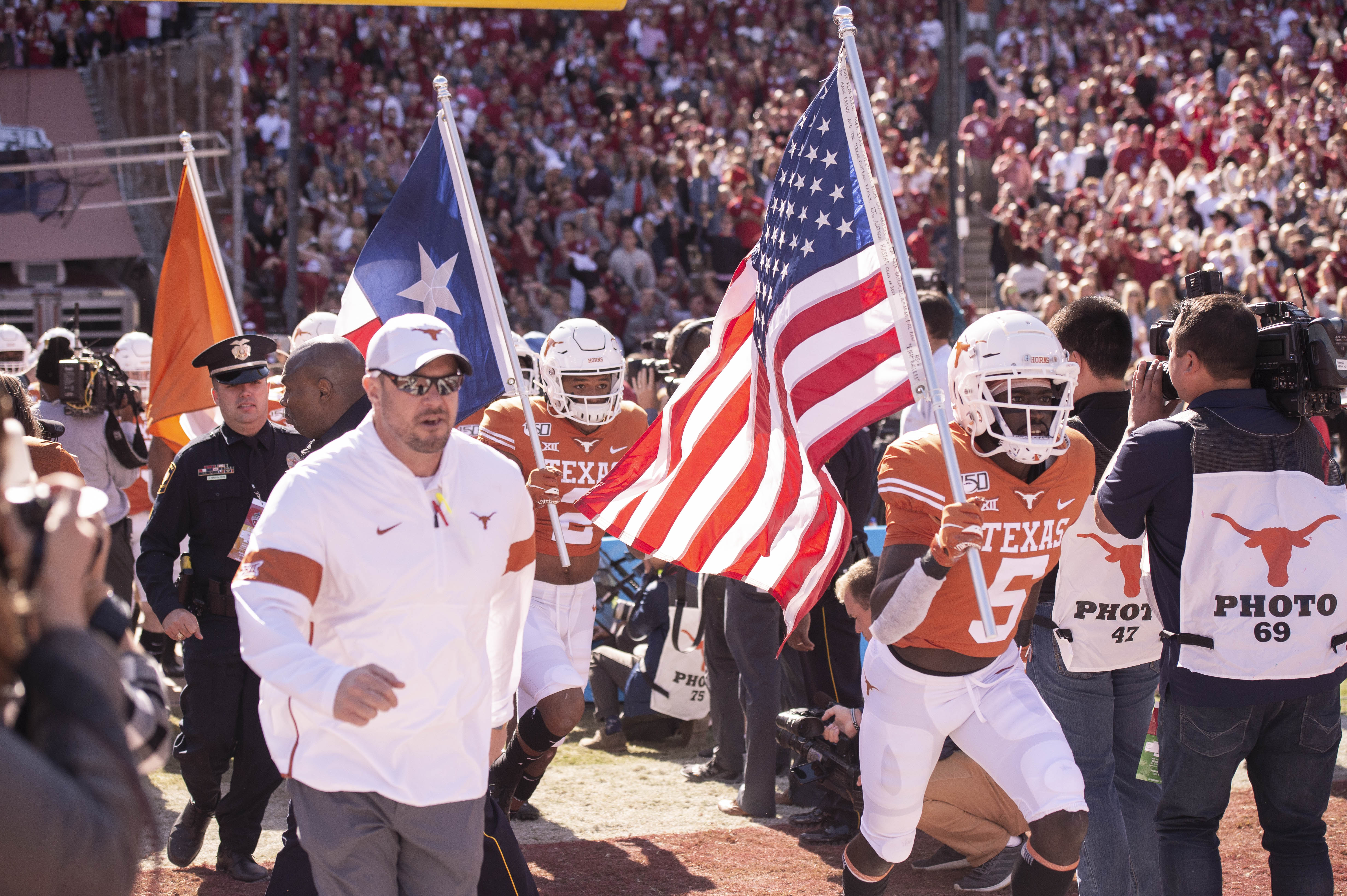 Texas Coach Tom Herman with team field-level